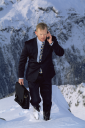 Royalty Free Photo of a Businessman on a Mountain With a Cellphone