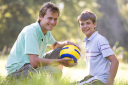 Royalty Free Photo of a Young Man and Boy With a Soccer Ball
