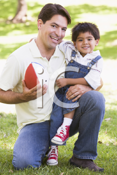 Royalty Free Photo of a Man and Boy Outside With a Football