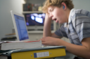 Royalty Free Photo of a Boy at a Laptop Listening to Music and Yawning