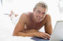 Royalty Free Photo of a Man Lying in Bed With a Laptop