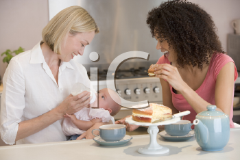 Royalty Free Photo of Two Women in a Kitchen With a Baby