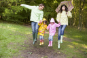 Royalty Free Photo of a Family Skipping in the Rain