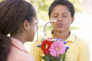 Royalty Free Photo of a Boy Giving a Girl Flowers and Puckering Up