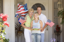 Royalty Free Photo of a Family at the Front Door With American Flags and Cookies