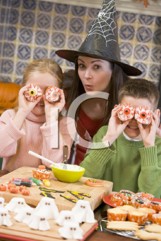 Royalty Free Photo of a Woman in a Witches Hat With Two Children Making Halloween Treats