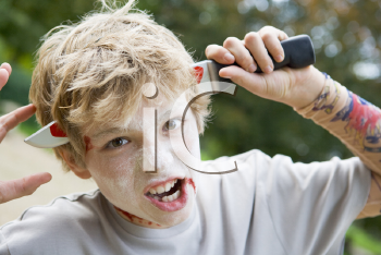 Royalty Free Photo of a Young Boy With a Halloween Gag Knife in His Head