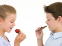 Royalty Free Photo of a Girl Eating a Strawberry and a Boy Eating a Chocolate Bar
