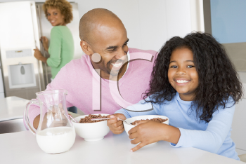 Royalty Free Photo of a Father and Daughter Having Breakfast With the Mother Behind Them