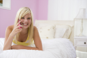 Royalty Free Photo of a Teenage Girl With a Cellphone in Her Bedroom