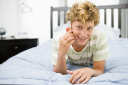 Royalty Free Photo of a Boy Using a Cellphone in His Room