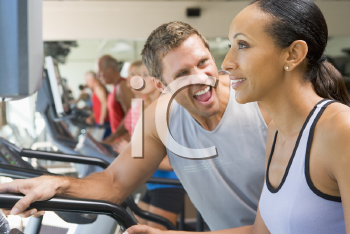 Royalty Free Photo of a Personal Trainer Encouraging a Woman on a Treadmill