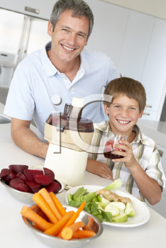 Royalty Free Photo of a Father and Son Making Vegetable Juice