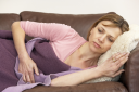 Royalty Free Photo of a Woman Lying on a Sick Woman on the Couch