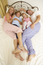Family Relaxing On Bed At Home