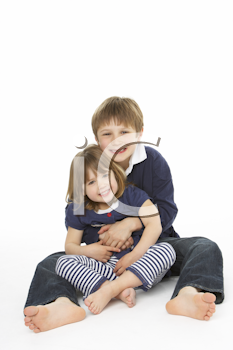Studio Portrait Of Happy Brother And Sister