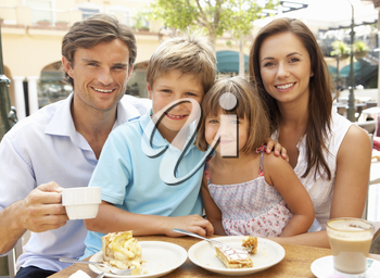 Young Family Enjoying Cup Of Coffee And Cake In Caf� Together