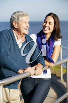 Senior Man With Adult Daughter Looking Over Railing At Sea