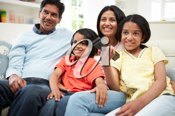 Indian Family Sitting On Sofa Watching TV Together