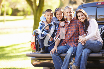 Family Sitting In Pick Up Truck On Camping Holiday