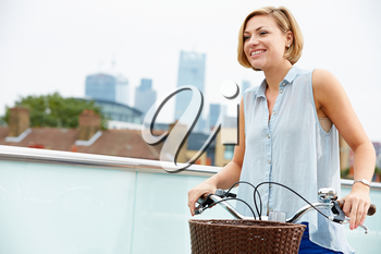 Woman Pushing Bike With City Skyline In Background
