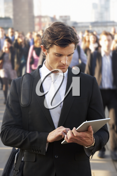 Male commuter in crowd using tablet