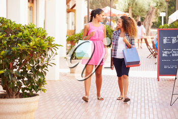 Two Female Friends Walking Along Street With Shopping Bags