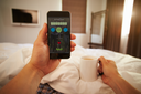 Man In Bed Looking At Health Monitoring App On Mobile Phone