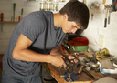 Teenage Boy Using Workbench In Garage