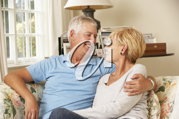 Mature Couple Sitting On Sofa At Home Together