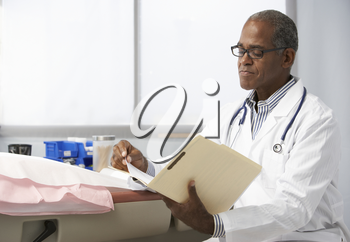 Male Doctor In Surgery Reading Patient Notes