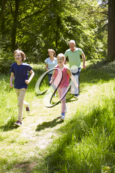 Grandparents With Grandchildren Running Through Countryside