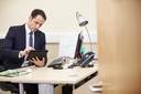 Male Consultant Using Digital Tablet At Desk In Office