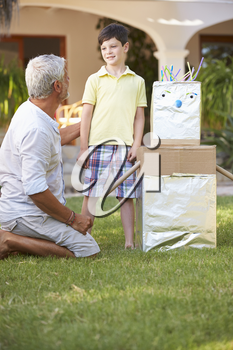 Grandfather And Grandson Building Model Robot In Garden