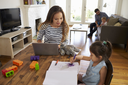 Mother Uses Laptop Whilst Father Plays With Children At Home