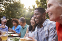 Group Of Mature Friends Enjoying Outdoor Meal In Backyard