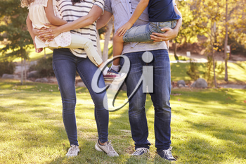 Parents Carrying Son And Daughter As They Play In Park