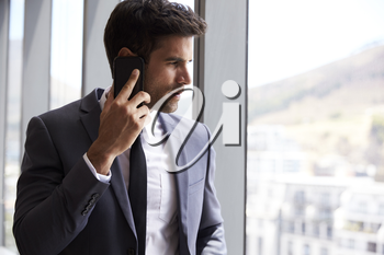 Businessman Making Phone Call Standing By Office Window