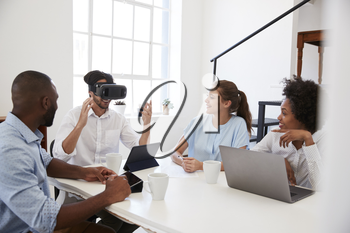 Man in VR goggles at a desk watched by colleagues in office