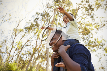 Father Carrying Son On Shoulders As They Walk In Park