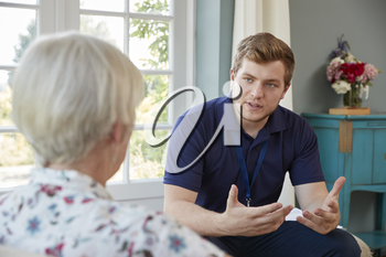 Senior woman talking with male care worker on home visit
