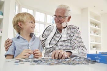 Senior man and grandson doing a jigsaw puzzle at home