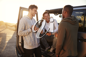 Three male friends on a road trip using a tablet computer