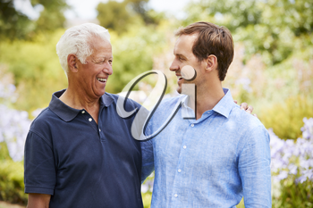 Senior Father With Adult Son On Walk In Park