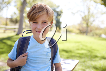 Young white schoolboy with backpack smiling to camera