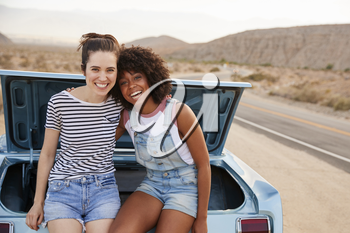Portrait Of Two Female Friends Sitting In Trunk Of Classic Car On Road Trip