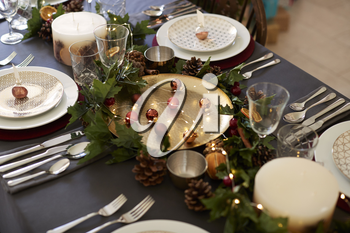 Christmas table setting with bauble name card holders arranged on plates, golden plate centrepiece with baubles, and green and red table decorations, elevated view