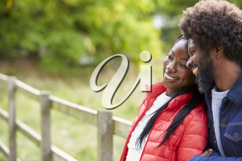 Black adult woman leaning on the shoulder of her boyfriend, standing in the countryside, close up