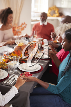 Multi generation mixed race family holding hands and saying grace before eating at their Thanksgiving dinner table, selective focus, vertical