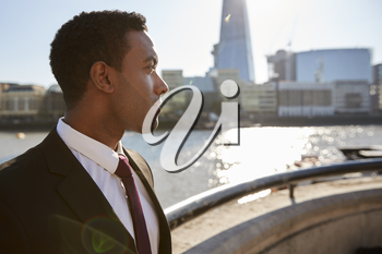 Young black businessman wearing shirt and tie standing by the River Thames, London, looking away, backlit